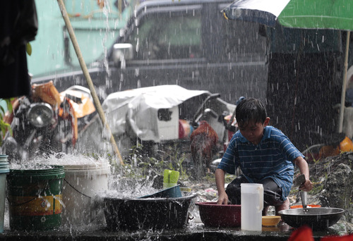 A Filipino boy cleans dishes at a temporary evacuation center as rain pours in suburban San Mateo, east of Manila, Philippines on Wednesday, Aug. 21, 2013. Earlier this week Tropical Storm Trami wreaked havoc in the country, causing eight deaths and severely flooding wide swaths of the capital Manila. Trami is bearing down on heavily populated northern Taiwan, prompting schools and offices to close.  (AP Photo/Aaron Favila)
