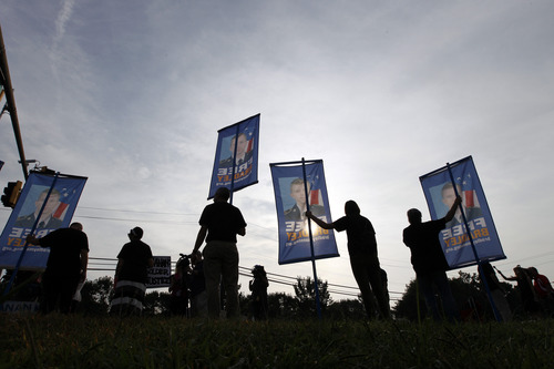 Supporters of Army Pfc. Bradley Manning hold up banners as they protest outside of the gates at Fort Meade, Md., Wednesday, Aug. 21, 2013, before a sentencing hearing at Manning's court martial. The military judge overseeing Manning's trial said she will announce on Wednesday his sentence for giving reams of classified information to WikiLeaks. (AP Photo/Jose Luis Magana)