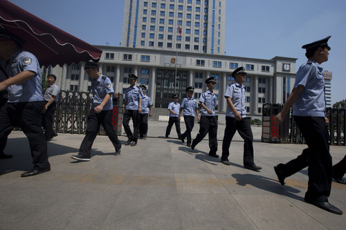 Chinese police officers march out of the Jinan Intermediate People's Court in Jinan in eastern China's Shandong province on Wednesday, Aug. 21, 2013.  Former Chinese politician Bo Xilai will stand trial at the court on Thursday on charges of corruption and abuse of power. (AP Photo/Ng Han Guan)
