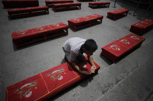 A man offers prayers to his deceased relatives on the Ghost Festival at Longhua Temple in Shanghai, China, Wednesday, Aug. 21, 2013. The festival is to worship ancestors in China. (AP Photo/Eugene Hoshiko)