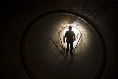 Paul Fraughton  |   The Salt Lake Tribune A worker looks into a section of the Parley's Canyon culvert project, which is halfway complete. When finished, the pipe will stretch for two miles down the canyon.                             Wednesday, August 21, 2013