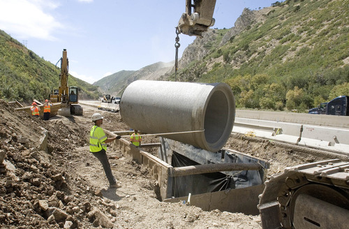 Paul Fraughton  |   The Salt Lake Tribune Workers prepare to lower a 12-foot section of concrete pipe into place on the Parley's Canyon culvert project. The workers are averaging around nine sections a day and are halfway finished. When complete, the pipe will stretch for two miles down the canyon.  Wednesday, August 21, 2013