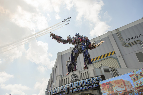 FILE - This June 20m 2013 file photo originally released by Universal Orlando shows a three-story-tall Optimus Prime figure at the entrance to the Transformers: The Ride-3D as a formation of private jets flies overhead at the grand opening of the attraction at Universal Orlando Resort in Orlando, Fla. This is one of several attractions that opened at theme parks this summer. (AP Photo/Universal Orlando Resort, File)