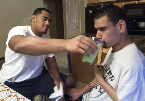 Steve Griffin | The Salt Lake Tribune  Bryan Mone, left, helps his brother, Filimone, eat his dinner at their home in Rose Park, Utah Aug. 20, 2013. Filimone is severely  handicapped and needs assistance to eat. Bryan, who is a top football recruit and plays football for Highland High School, has maintained a close relationship with his brother and family.