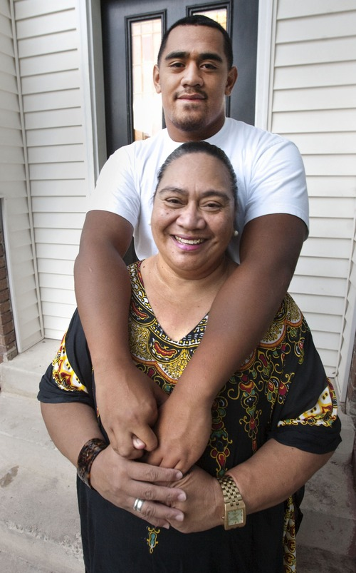 Steve Griffin | The Salt Lake Tribune  Bryan Mone wraps his arms around his mother, Sela Mone, at their home in Rose Park, Aug. 20, 2013. Bryan, who is a top football recruit and plays football for Highland High School, has maintained a close relationship with family.