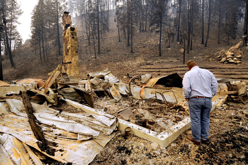 U.S. Sen. Jon Tester, D-Mont., looks at the remains of a Lolo Creek home that was destroyed by the West Fork II fire when it swept down the Lolo Creek canyon, Wednesday, Aug. 21, 2013 near Lolo, Mont. The fire burned four other homes as well along the U.S. Highway 12 corridor. (AP Photo/Missoulian, Kurt Wilson)