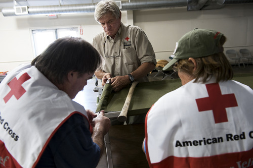 Red Cross volunteers Mike Dabkowski of Sonora middle, Brian Clemetson of Murphys, left, and Koya Andrews of Soulsbyville, right, build sleeping cots at the shelter at the Mother Lode Fairgrounds in Sonora, Calif., with the expectation that residents from Pine Mountain Lake will flee the Rim Fire, Wednesday, Aug. 21, 2013. (AP Photo/The Modesto Bee, Andy Alfaro) LOCAL TV OUT (KXTV10, KCRA3, KOVR13, FOX40, KMAX31, KQCA58, CENTRAL VALLEY TV); LOCAL PRINT OUT (TURLOCK JOURNAL, CERES COURIER, OAKDALE LEADER, MODESTO VIEW, PATTERSON IRRIGATOR, MANTECA BULLETIN, RIPON, RECROD, SONORA UNION DEMOCRAT, AMADOR LEDGER DISPATCH, ESCALON TIMES, CALAVERAS ENTERPRISE, RIVERBANKS NEWS) LOCAL INTERNET OUT (TURLOCK CITY NEWS.COM, MOTHER LODE.COM)