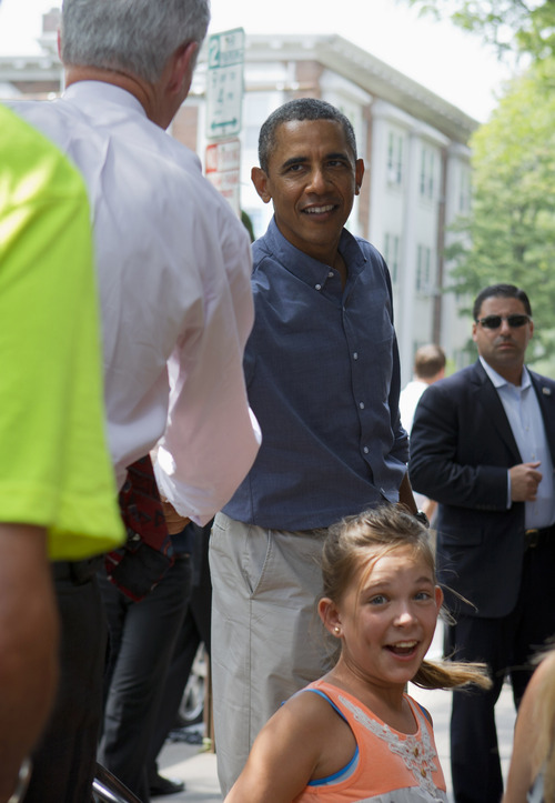 Rubi Platt, 11, of Orange County, Calif., reacts as President Barack Obama shakes hands behind her during his stop at Magnolia's Deli and Cafe in Rochester, N.Y., Thursday, Aug. 22, 2013, to talk with college students and their parents on the first day of a two-day bus tour where he is speaking about college financial aid. (AP Photo/Jacquelyn Martin)