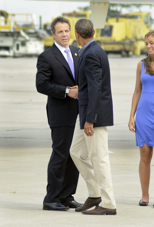 New York State Gov. Andrew Cuomo shakes hands with President Barack Obama after Obama arrived at Buffalo Niagara International Airport in Buffalo, N.Y.,, Thursday, August 22, 2013. (AP photos/Heather Ainsworth)