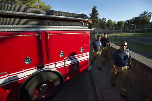 Shawn Woottenn and other members of the Lathrop-Manteca fire department wait in the town of Tuolumne, Calif, Friday Aug. 23, 2013. The town is under advisory evacuation as the Rim Fire grows in size.(AP Photo/The Modesto Bee, Andy Alfaro) NO SALES, NO MGS, NO TV, ONLINE AP MEMBERS ONLY
