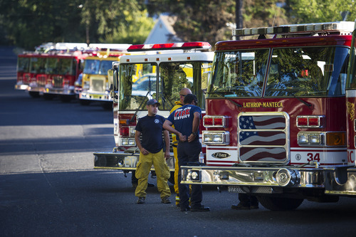 Firefighters wait in the town of Tuolumne, Calif, Friday Aug. 23, 2013. The town is under advisory evacuation as the Rim Fire grows in size.(AP Photo/The Modesto Bee, Andy Alfaro) NO SALES, NO MGS, NO TV, ONLINE AP MEMBERS ONLY