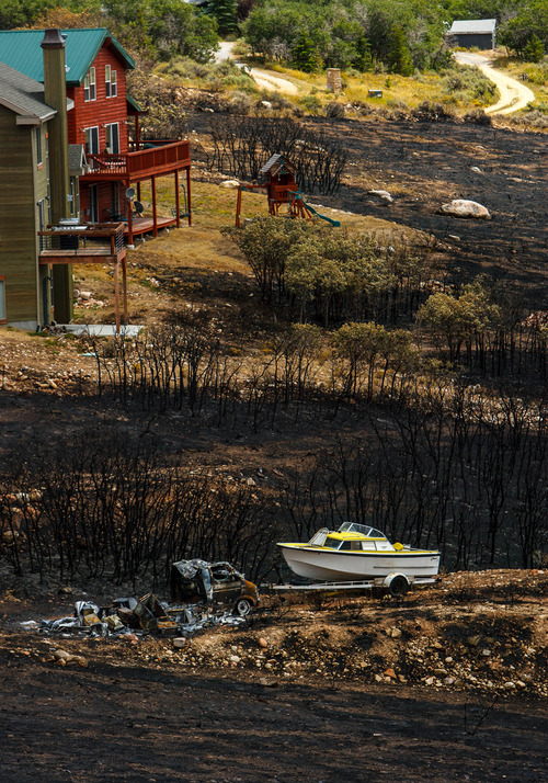 Trent Nelson  |  The Salt Lake Tribune Homes spared from the fire in the Lake Rockport Estates, Thursday August 22, 2013. A Utah program requires new construction to reduce brush and trees around houses. This fuels mitigation strategy creates a defensible space so that wildfires have a decreased chance of burning structures.