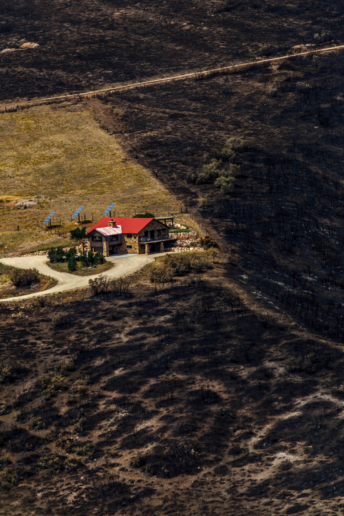 Trent Nelson  |  The Salt Lake Tribune A home spared from the fire in the Lake Rockport Estates, Thursday August 22, 2013. A Utah program requires new construction to reduce brush and trees around houses. This fuels mitigation strategy creates a defensible space so that wildfires have a decreased chance of burning structures.