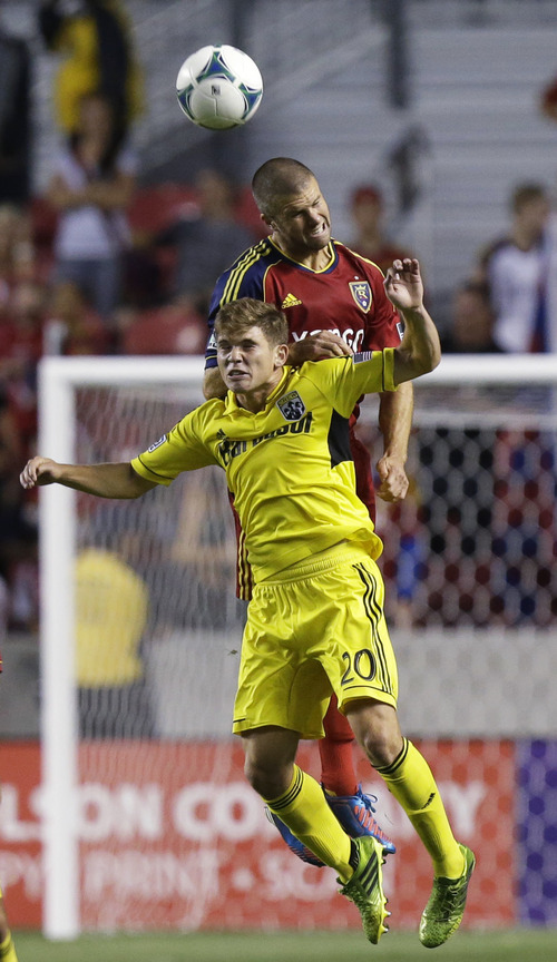 Real Salt Lake's Chris Wingert, rear, heads the ball as Columbus Crew's Wil Trapp (20) defends in the first half during an MLS soccer game Saturday, Aug. 24, 2013, in Sandy, Utah. (AP Photo/Rick Bowmer)