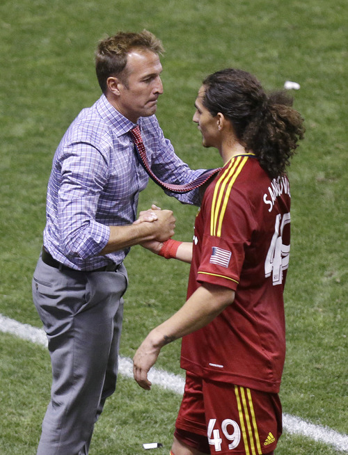 Real Salt Lake head coach Jason Kreis, left, shakes the hand of player Devon Sandoval, right, as he leaves the game against the Columbus Crew in the second half of an MLS soccer game, Saturday, Aug. 24, 2013, in Sandy, Utah. Real Salt Lake won 4-0. (AP Photo/Rick Bowmer)