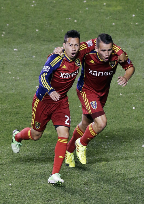 Real Salt Lake's Luis Gil, right, celebrates with teammate Sebastian Velasquez, left, after scoring against the Columbus Crew in the second half during an MLS soccer game, Saturday, Aug. 24, 2013, in Sandy, Utah. Real Salt Lake defeated the Columbus Crew 4-0. (AP Photo/Rick Bowmer)