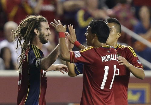 Real Salt Lake's Kyle Beckerman, left, celebrates with teammates Javier Morales (11) and Carlos Salcedo, rear, after scoring in the first half during an MLS soccer game against the Columbus Crew on Saturday, Aug. 24, 2013, in Sandy, Utah.  (AP Photo/Rick Bowmer)