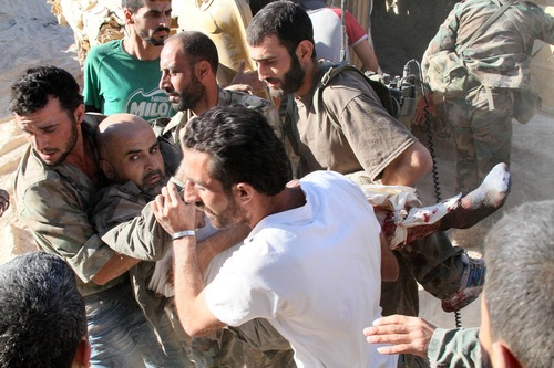 """In this photo taken on a government organized media tour, Syrian army soldiers evacuate their commander who was injured during heavy clashes with Syrian rebels in the Jobar neighborhood of Damascus, Syria, Saturday, Aug. 24, 2013. Syrian state media accused rebels of using chemical arms on Saturday against government troops trying to storm a contested neighborhood of Damascus, claiming a major army offensive in recent days had forced the opposition fighters to resort to such weapons """"as their last card."""" State TV broadcast images of plastic jugs, gas masks, vials of an unspecified medication, explosives and other items that it said were seized from rebel hideouts. It did not, however, show any video of soldiers reportedly affected by toxic gas in the fighting in the Jobar neighborhood of Damascus. (AP Photo)"""