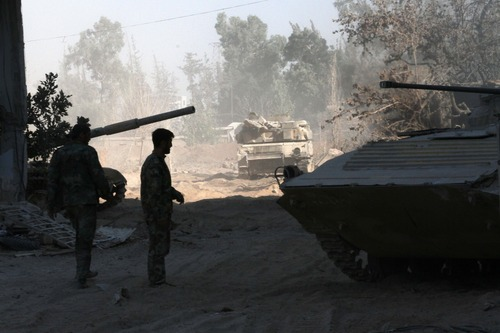 """In this photo taken on a government organized media tour, Syrian army soldiers are seen deployed in the Jobar neighborhood of Damascus, Syria, Saturday, Aug. 24, 2013. Syrian state media accused rebels of using chemical arms on Saturday against government troops trying to storm a contested neighborhood of Damascus, claiming a major army offensive in recent days had forced the opposition fighters to resort to such weapons """"as their last card."""" State TV broadcast images of plastic jugs, gas masks, vials of an unspecified medication, explosives and other items that it said were seized from rebel hideouts. It did not, however, show any video of soldiers reportedly affected by toxic gas in the fighting in the Jobar neighborhood of Damascus. (AP Photo)"""