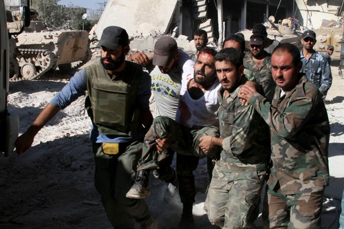 """In this photo taken on a government organized tour, Syrian army soldiers evacuate a comrade injured during heavy clashes with Syrian rebels in the Jobar neighborhood of Damascus, Syria, Saturday, Aug. 24, 2013. Syrian state media accused rebels of using chemical arms on Saturday against government troops trying to storm a contested neighborhood of Damascus, claiming a major army offensive in recent days had forced the opposition fighters to resort to such weapons """"as their last card."""" State TV broadcast images of plastic jugs, gas masks, vials of an unspecified medication, explosives and other items that it said were seized from rebel hideouts. It did not, however, show any video of soldiers reportedly affected by toxic gas in the fighting in the Jobar neighborhood of Damascus. (AP Photo)"""