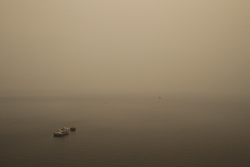A small boat floats on the Hetch Hetchy Reservoir as the smoke and some embers from the Rim Fire fill the air in Yosemite National Park, Calif., on Sunday, Aug. 25, 2013. With winds gusting to 50 mph on Sierra mountain ridges and flames jumping from treetop to treetop, hundreds of firefighters have been deployed to protect this and other communities in the path of the Rim Fire raging north of Yosemite National Park. (AP Photo/Jae C. Hong)