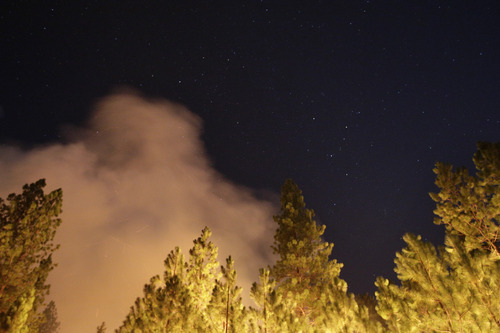 The smoke generated by the Rim Fire rises under a star-filled sky near Yosemite National Park, Calif., on Sunday, Aug. 25, 2013. Fire crews are clearing brush and setting sprinklers to protect two groves of giant sequoias as a massive week-old wildfire rages along the remote northwest edge of Yosemite National Park. (AP Photo/Jae C. Hong)