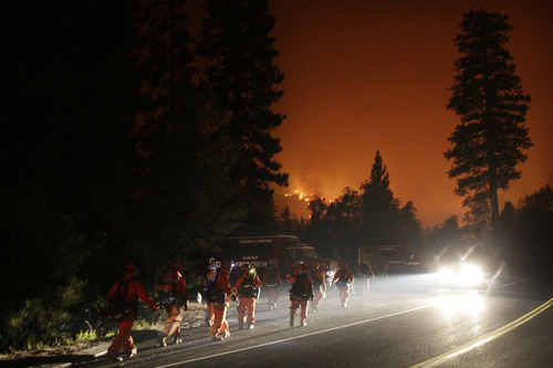 Firefighters walk toward their trucks as the Rim Fire continues to burn near Yosemite National Park, Calif., on Saturday, Aug. 24, 2013. Fire crews are clearing brush and setting sprinklers to protect two groves of giant sequoias as a massive week-old wildfire rages along the remote northwest edge of Yosemite National Park. (AP Photo/Jae C. Hong)