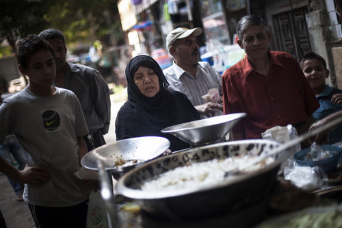An Egyptian woman waits for her breakfast on a street fast food restaurant in Suleiman Gohar market in Dokki district in Cairo, Egypt, Monday, Aug. 26, 2013. Egypt's recent turmoil has scared away tourists and affected the livelihood of the one in eight Egyptians who earn their living from tourism. An evening curfew imposed by the military to quell protests has further choked many businesses, such as restaurants, stores and entertainment venues, serving another blow to the country's already battered economy.  (AP Photo/Manu Brabo)