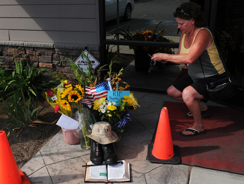 In this Aug. 22, 2013, photo, Lill Duncan takes a photo of a memorial for Delbert Belton, an 88-year-old World War II veteran who was beaten to death, in Spokane, Wash. Police have arrested one of two teens suspected of fatally beating Belton, who had survived the battle for Okinawa, and the police chief said Friday, Aug. 23, that the brutal attack does not appear to have been racially motivated. (AP Photo/The Spokesman-Review, Tyler Tjomsland)