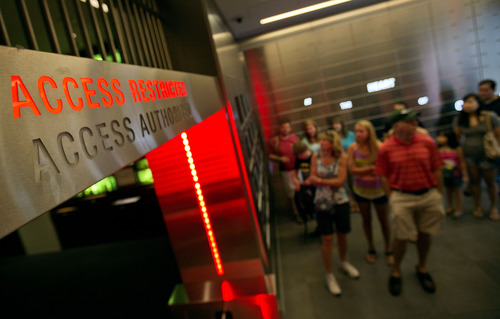 """In this Friday, Aug. 9, 2013 photo, a tour group enters the vault exhibit containing the """"secret recipe"""" for Coca-Cola at the World of Coca-Cola museum, in Atlanta. The 127-year-old recipe for Coke sits inside an imposing steel vault that's bathed in red security lights, while security cameras monitor the area to make sure the fizzy formula stays a secret. (AP Photo/David Goldman)"""