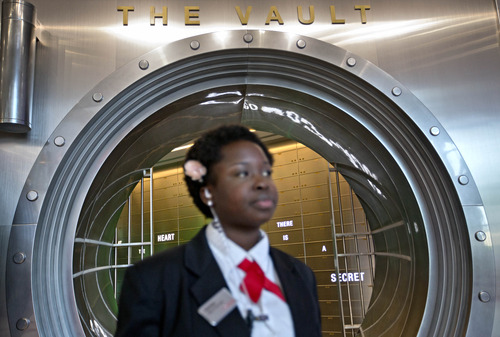 """In this Friday, Aug. 9, 2013 photo, Marilyn Buamah, a secret formula security officer, stands outside the vault containing the """"secret recipe"""" for Coca-Cola while waiting for a tour group at the World of Coca-Cola museum, in Atlanta. The 127-year-old recipe for Coke sits inside an imposing steel vault that's bathed in red security lights, while security cameras monitor the area to make sure the fizzy formula stays a secret. (AP Photo/David Goldman)"""