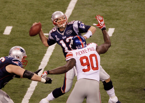 New England Patriots quarterback Tom Brady (12) throws the last pass of the game as New York Giants defensive end Jason Pierre-Paul (90) defends during the second half of the NFL Super Bowl XLVI football game, Sunday, Feb. 5, 2012, in Indianapolis. (AP Photo/Charlie Riedel)