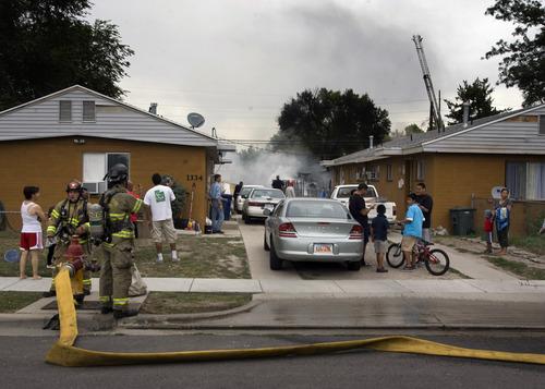 Rick Egan  | The Salt Lake Tribune   Neighbors watch firefights as they fight a fire on 1300 West near Arapahoe Avenue,  in Salt Lake City, Monday, August 26, 2013.