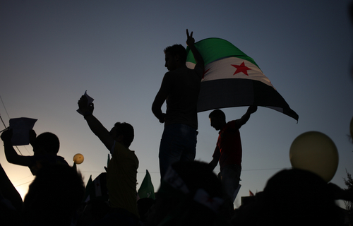 Syrians wave the Syrian revolutionary flag during a protest in front of the Syrian embassy in Amman, Jordan, to condemn the alleged poison gas attack on the suburbs of Damascus, Friday, Aug. 23, 2013.  Anti-government activists accused the Syrian regime of carrying out a toxic gas attack that is thought to have killed at least 100 people, including many children as they slept, during intense artillery and rocket barrages Wednesday on the eastern suburbs of Damascus. (AP Photo/Mohammad Hannon)