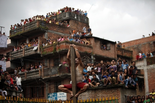 A Nepalese climbs a pole erected in a pond as part of Deopokhari festival in Katmandu, Nepal, Friday, Aug. 23, 2013. The festival is held to appease, what locals believe, a demon in the pond. Every year on this day cattle is sacrificed to the pond demon so that no human lives are lost drowning in the pond, a common occurrence before the festival began, according to locals. (AP Photo/Niranjan Shrestha)