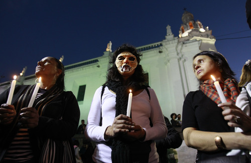 A woman wearing a mask in the likeness of a tigrillo, joins with others in a candlelight vigil, in protest against the government's decision to allow oil drilling in the Amazon reserve, Yasuni National Park, in Quito, Ecuador, Thursday, Aug. 22, 2013. (AP Photo/Dolores Ochoa)
