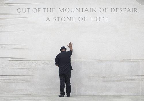 Rev. Bobby Turner or Columbus, Ohio, places his hand on the Martin Luther King Jr. Memorial, Thursday, Aug. 22, 2013, in Washington. President Barack Obama is scheduled to speak at a ceremony on the 50th anniversary of the 1963 March on Washington. (AP Photo/Carolyn Kaster)