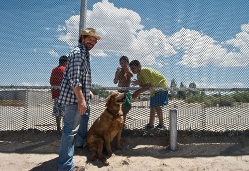 In this 2010 photo provided by Explore.org,, philanthropist Charlie Annenberg, left, stands with his golden retriever, Lucky, while filming a documentary at the Mexican border of Ciudad Juarez, the border town with El Paso, Texas. For 16 years, Lucky has been his sidekick, soul mate and inspiration, said Annenberg.  In 2010, Annenberg started Dog Bless You, a journal of their travels as told by Lucky but written by Annenberg. (AP Photo/Explore.org)