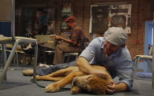 """In this Oct. 2011 photo provided by Explore.org, philanthropist Charlie Annenberg, right, plays with his golden retriever, Lucky, as blues musician James """"Super Chikan"""" Johnson, middle, plays inside the Delta Blues Museum in Clarksdale, Miss. For 16 years, Lucky has been his sidekick, soul mate and inspiration, said Annenberg, who created  Dog Bless You, a journal of their travels as told by Lucky but written by Annenberg. (AP Photo/Explore.org)"""