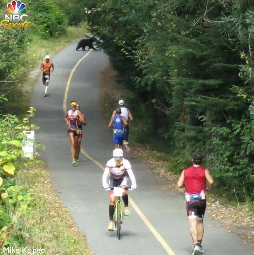 Salt Lake City's Marc Rosello, in orange, runs on after encountering a black bear in Whistler, B.C., on Sunday. (Courtesy of NBC)