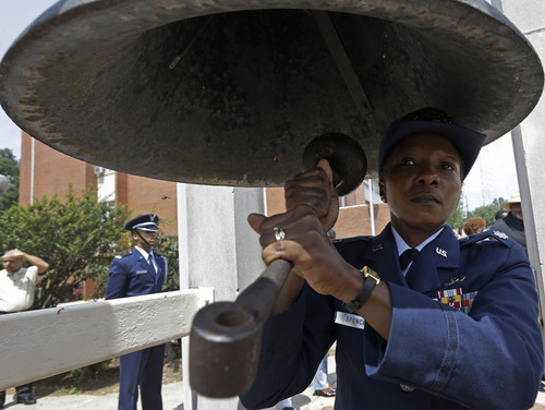 """ROTC Lt. Col. Tangela Spencer rings the bell 50 times as elementary students recite verses from the """"I Have a Dream"""" speech given 50 years ago by Rev. Martin Luther King. About 500 students and others gathered for the event in Montgomery, Ala., Wednesday, Aug. 28, 2013 on the campus of Alabama State University to honor the 50th anniversary of the March on Washington. (AP Photo/Dave Martin)"""