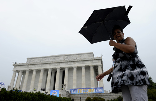 A person walks in the rain past the Lincoln Memorial in Washington, Wednesday, Aug. 28, 213, during the 50th anniversary of the March on Washington. President Barack Obama will speak later Wednesday. (AP Photo/Susan Walsh)