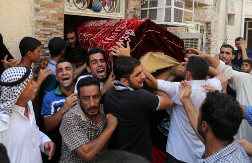 Mourners carry the coffin of Ali Abd al-Razzaq, 25, who was killed when a parked car bomb hit a coffee shop in the largely Sunni neighborhood of Azamiyah on Wednesday, in Azamiyah, Baghdad, Iraq, Thursday, Aug. 29, 2013. Car bomb blasts and other explosions tore through the Baghdad area Wednesday in a day of violence that killed and wounded scores of civilians, intensifying worries about Iraq's ability to tame the spiraling mayhem gripping the country. (AP Photo/Khalid Mohammed)