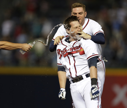 Atlanta Braves' Chris Johnson, front, celebrates with teammate Freddie Freeman, rear, after driving in the game-wining run with a single in the ninth inning of a baseball game against the Cleveland Indians in Atlanta Wednesday, Aug. 28, 2013. Atlanta won 3-2. (AP Photo/John Bazemore)