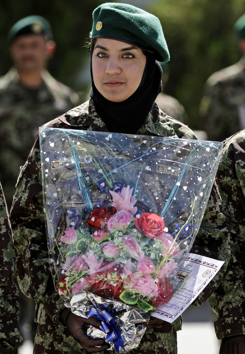 A new Afghan Army recruit holds flowers as she stands in formation during a graduation ceremony at the Afghan National Army base on the outskirts of Kabul, Afghanistan, Thursday, Aug. 29, 2013. (AP Photo/Ahmad Jamshid)