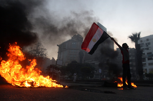 A supporter of Egypt's ousted President Mohammed Morsi, holds a national flag as he stands next to burning tires during a protest in Cairo, Egypt, Friday, Aug. 30, 2013. Thousands of protesters and Muslim Brotherhood supporters rallied Friday throughout Egypt against a military coup and a bloody security crackdown, though tanks and armored police vehicles barred them from converging in major squares. (AP Photo/Khalil Hamra)