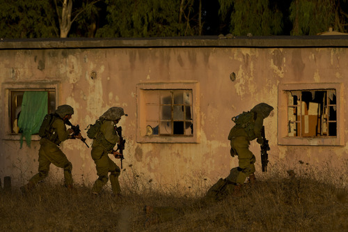 Israeli soldiers take part in a drill in the Golan Heights, near the border between the Israeli-controlled Golan Heights and Syria, Friday, Aug. 30, 2013. (AP Photo/Bernat Armangue)