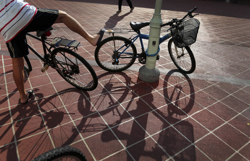 A man straddles his bicycle as another woman walks in a local market, Friday, Aug. 30, 2013 in Singapore. Most government housing developments in the city-state are self-contained and have local fresh markets and shops within walking distance in the neighborhood. (AP Photo/Wong Maye-E)