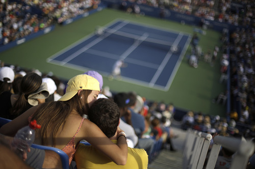 A couple shares a moment during the second round match between Andy Murray of Great Britain and Leonardo Mayer of Argentina at the 2013 U.S. Open tennis tournament, Friday, Aug. 30, 2013, in New York. (AP Photo/David Goldman)