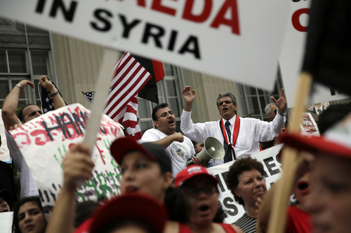 Members of the local Syrian community chant after marching in protest against the United States' involvement in Syria, Friday, Aug. 30, 2013, in Allentown, Pa. President Barack Obama says he hasn't made a final decision about a military strike against Syria_but is considering a limited and narrow action in response to a chemical weapons attack that he says Syria's government carried out last week. (AP Photo/Matt Slocum)